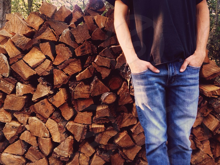 man standing on front of fire wood photo