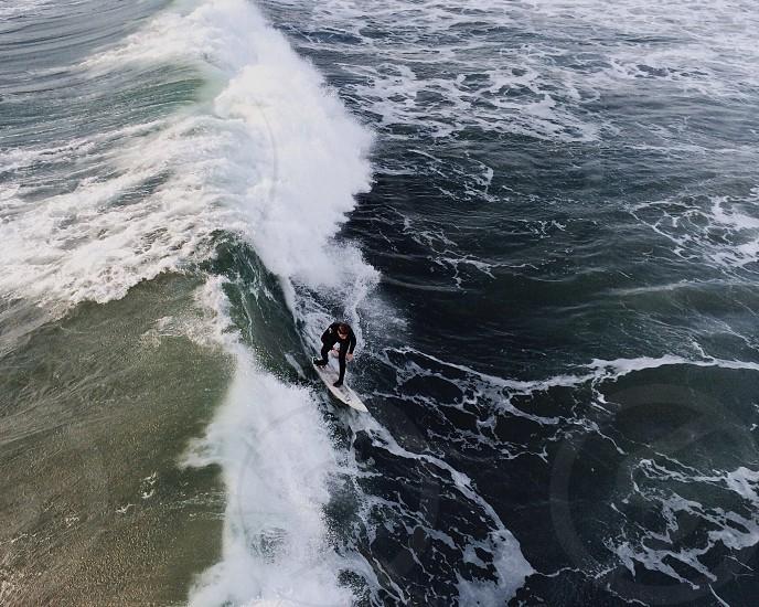 man in black scuba suit surfing photo