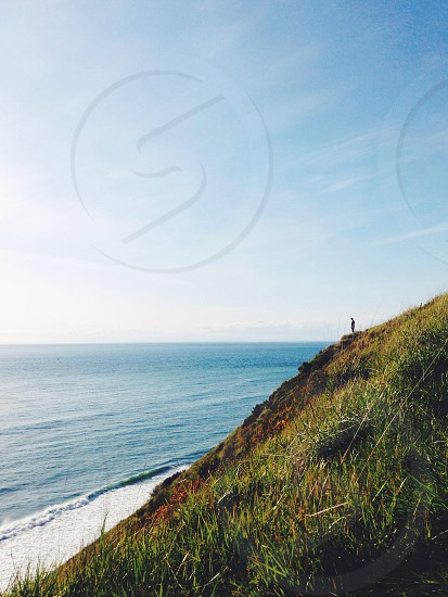 person standing on green hill overlooking ocean photo