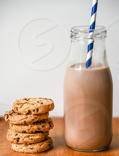 stacked 5 chocolate chip cookies beside clear glass jar with brown liquid and white blue waffle stick photo
