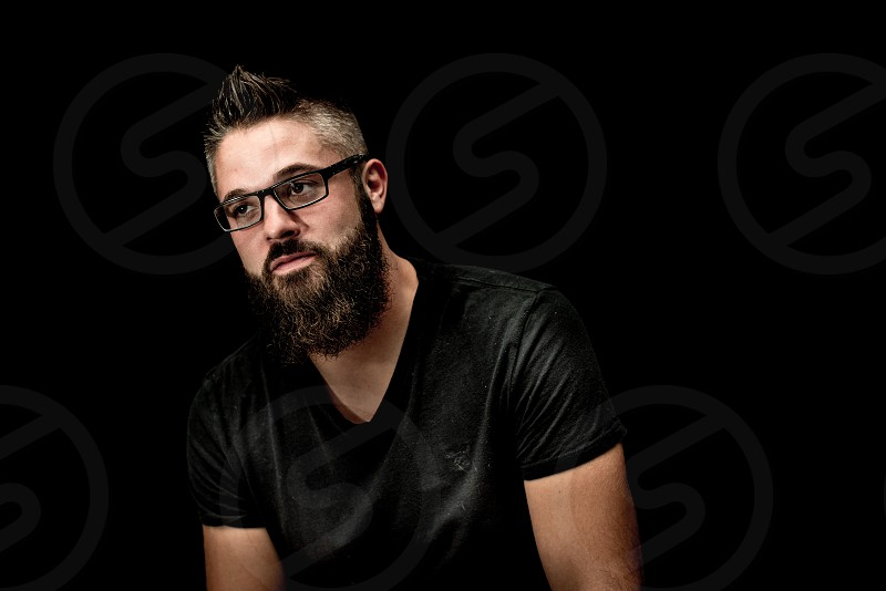 young adult male black background black t-shirt attractive beard rugged looking at camera glasses photo