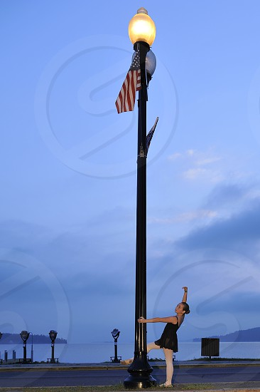 Early AM photo of young dancer giving thanks to all that have/are serving to protect us on Memorial Day. Flag Flying. photo
