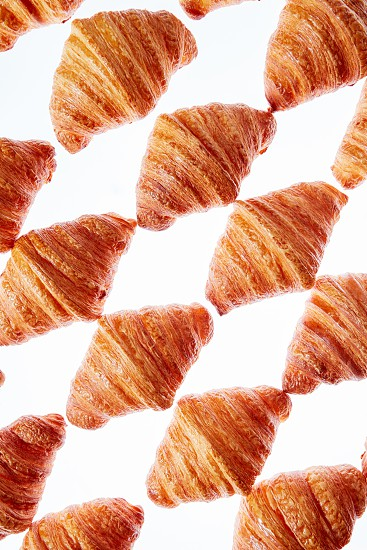 French homemade delicious bakeries - fresh croissants rhombus pattern on a white background. photo
