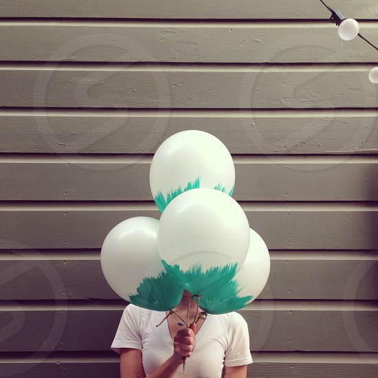 woman covering her face with 4 white and green balloons photo