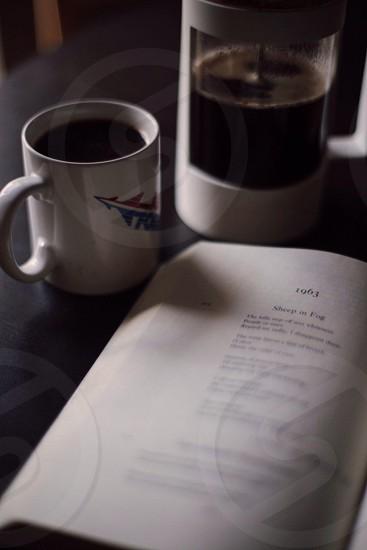 black liquid in white ceramic coffee mug beside white book photo