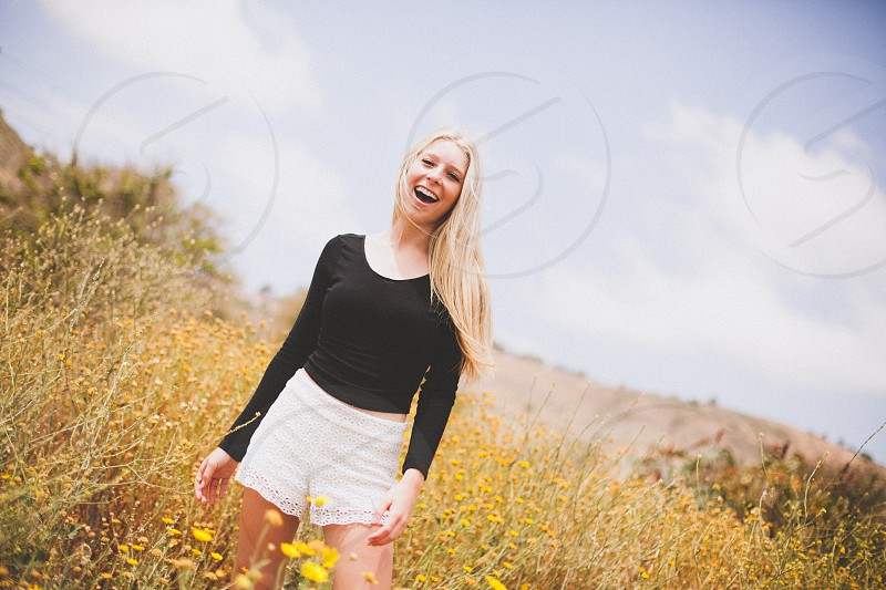 woman standing in the field wearing white short photo