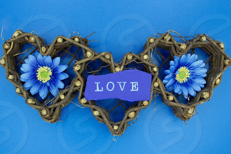 """Overhead view of three woven grapevine hearts with blue flowers on either side of the word """"LOVE"""" stamped in white ink in torn dark blue paper on a blue background photo"""
