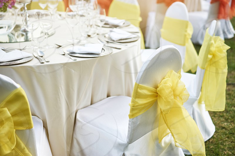 Back side of spandex white cover dining chairs with yellow organza sash settings for luxury wedding reception dinner table outdoor photo