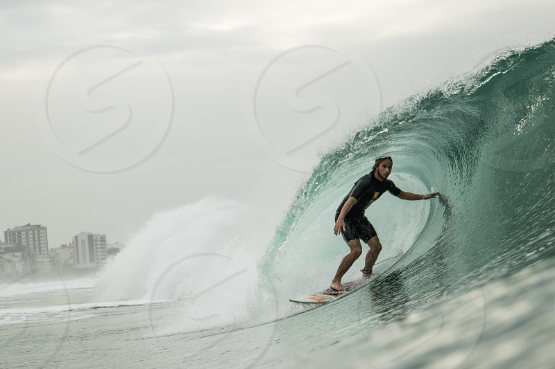 man in black t shirt surfing on the surfboard facing the big waves photography photo