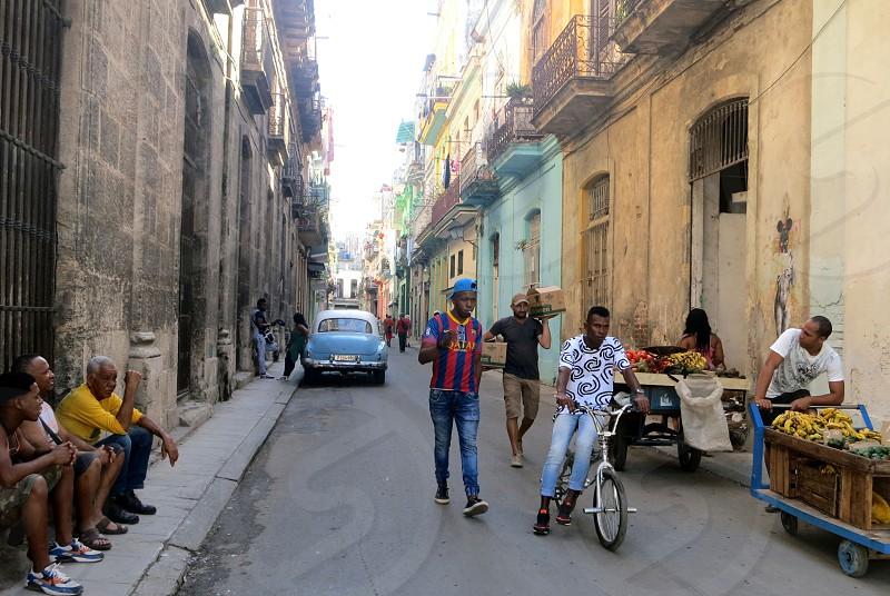 Street scene Havana Cuba; men sitting on stoop observing activity and vendors photo