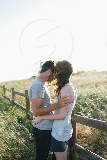 couples by a wooden fence photo