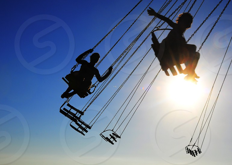 people riding amusement park swing ride photo