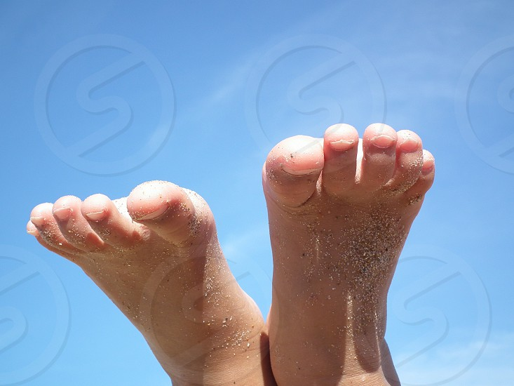 Child's feet up against the Spanish blue sky at the beach.  photo