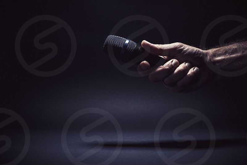 Conceptual composition male hand holding a microphone ready for an interview symbolically representing a freedom of speech. photo