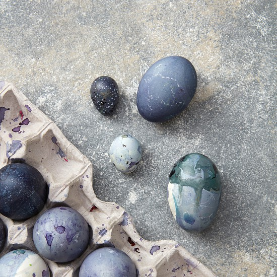 Many eggs of navy blue color represented in box over grey background. Beautiful composition of eggs foe making post card on Easter. photo