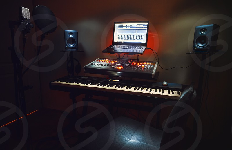 Interior of a small bedroom recording studio details of equipment microphone in foreground and modern mixing console with laptop in background.  photo