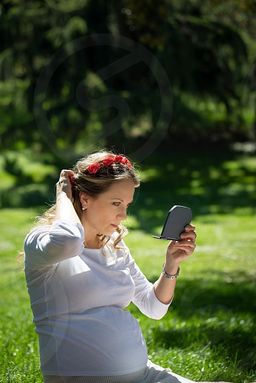 A happy young pregnant woman in a flower wreath and in bright clothes is sitting on a bright meadow in a summer park looking in a mirror and straightening her hair. photo