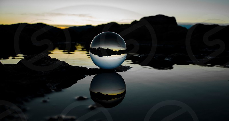 glass ball reflecting on water surface behind rock silhouette photo