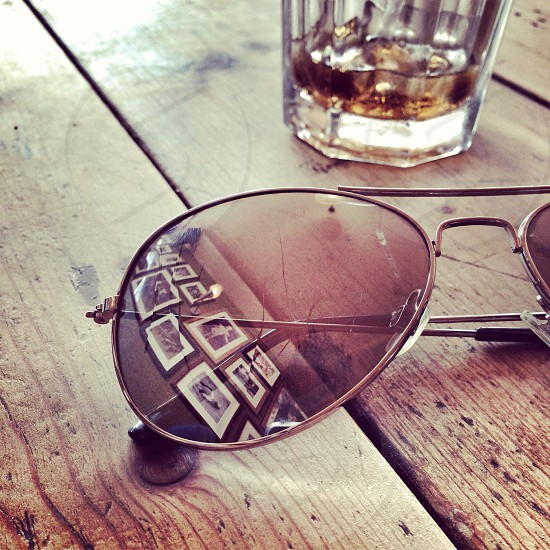 Reflection of framed photos in sunglasses on a table with a drink in the background  photo