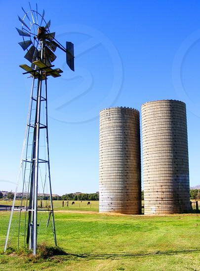 Vintage windmill stand near two grain silos photo