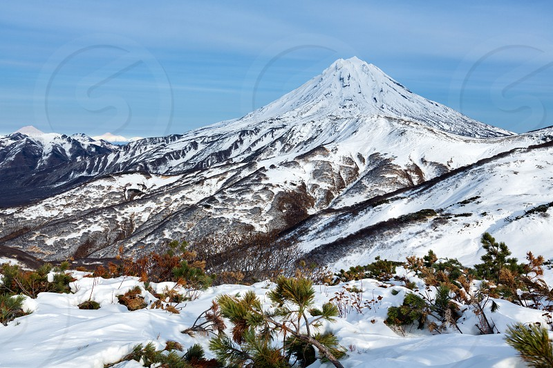 Wintry snowy mountainous landscape of Kamchatka Peninsula: beautiful view of snow-capped cone of Vilyuchinsky Volcano. Kamchatka Region Russian Far East Eurasia. photo