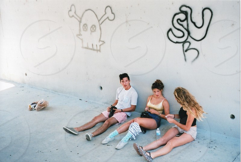 2 women and a man sitting by the wall photo