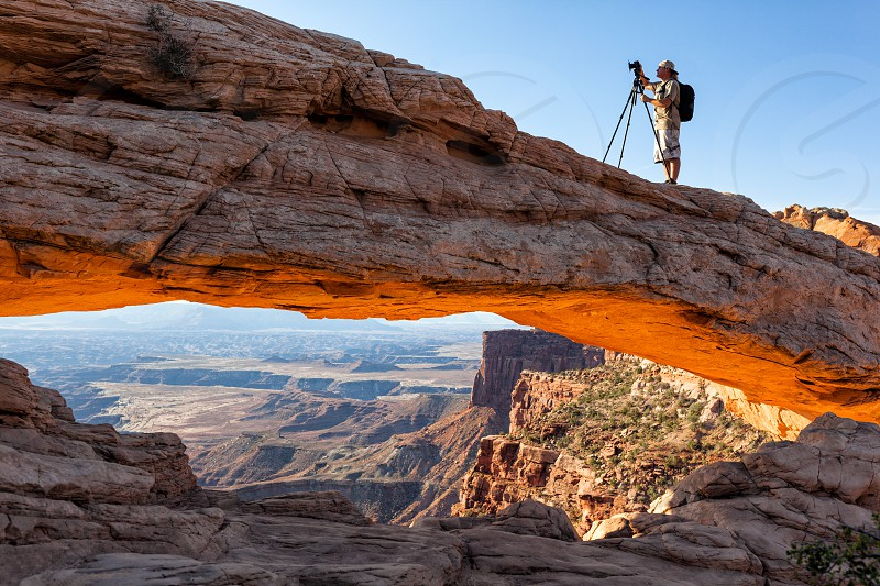 person in front of dslr camera with tripod on brown rocky mountain photo