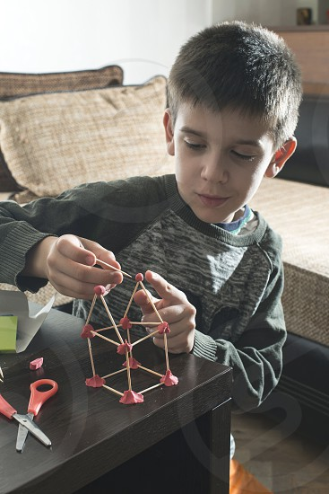 Child make house with wooden sticks and plasticine photo