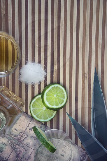 3 sliced lime beside iodized salt and clear glass decanter on brown beige table photo