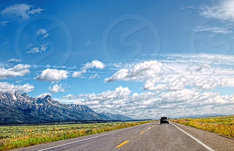 ca driving down a paved highway surrounded by green grass and white capped mountains under a white cloud blue sky photo
