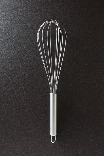 Metal whisk presented on a black concrete background with space for text.. Kitchen device for cooking different foods. Top view photo