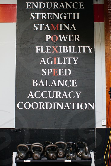 black kettle bells below a black red and white endurance strength stamina power flexibility agility speed balance accuracy coordination signage photo