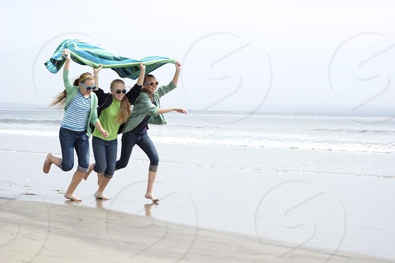 running beach friends fun summertime playful teens smiling racing playing energetic candid sand barefeet  photo