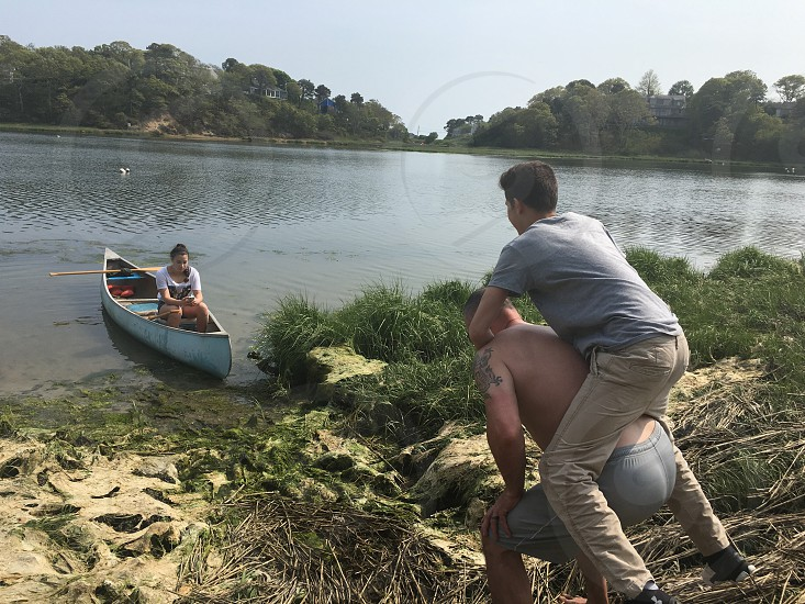 topless man carrying man in grey shirt and brown pants on rocky shore near canoe with woman in white shirt sitting during daytime photo