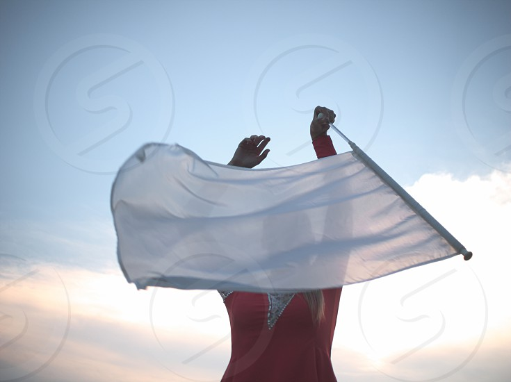 Blonde Teen Majorette Girl with White Flag Outdoors in Red Dress photo