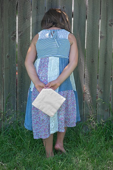 girl wearing a white blue and purple floral tank dress and holding a beige handkerchief photo