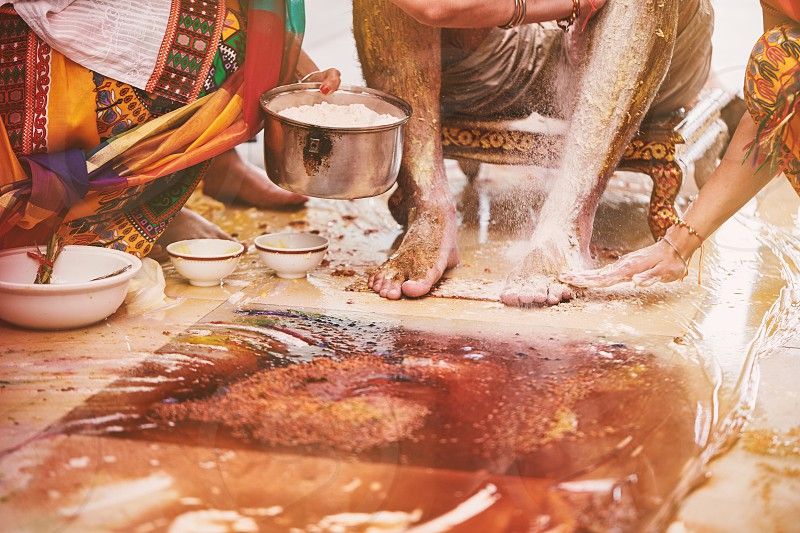 The groom sitting while the family and relatives members pasting turmeric powder (haldi) oil mixed with milk before bathing (snan) traditional rituals for Indian marriage photo