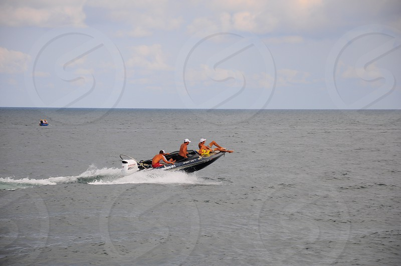 people riding on black speed boat photo