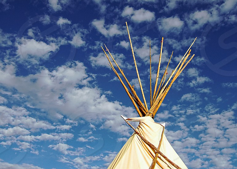 The top of a Native American tepee is seen against a blue sky with fluffy white clouds.   photo