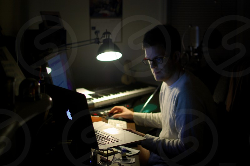 college student working late at night on a music project photo