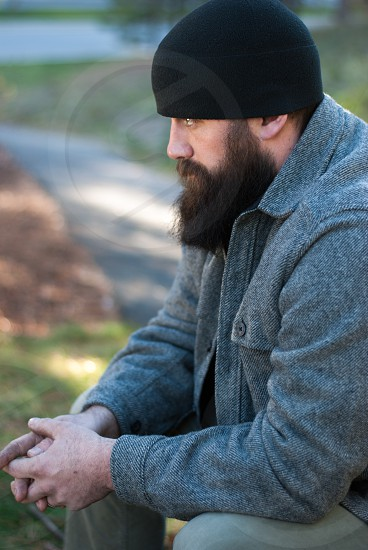 Bearded man with beanie sitting outdoors in the fall photo