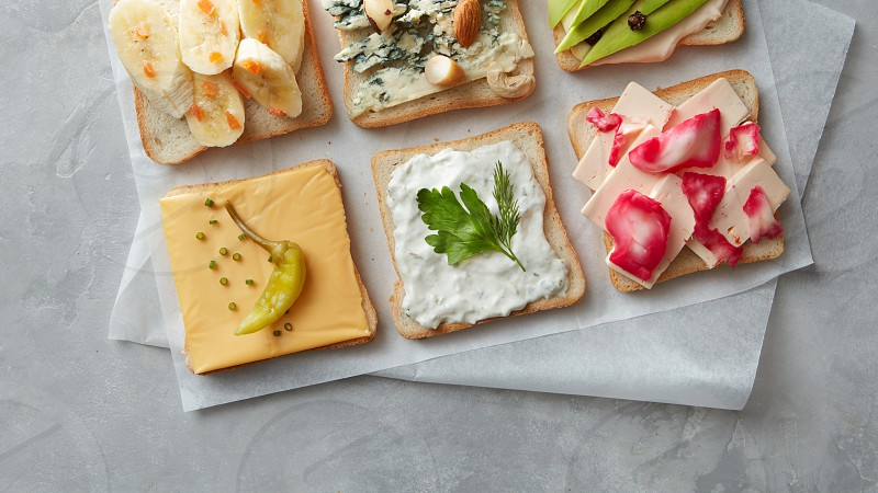 Different kinds of colorful sandwiches on white chalkboard background from above (top view). Party starter or appetizer - flat lay composition. photo