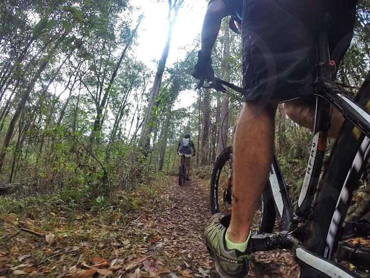 man wearing black shorts and brown cyclist shoes riding black mountain bike photo