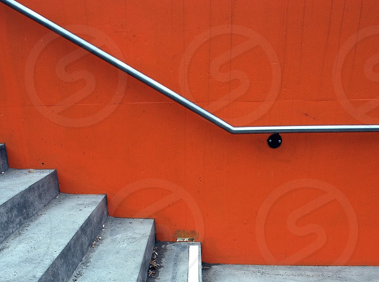 silver metal railings on orange painted wall with gray concrete stairs photo