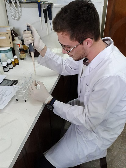 A handsome scientist working on the lab with a micro-pipette photo