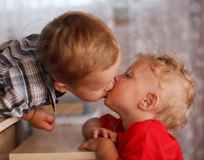 Two little brothers are kissing. Close up portrait. Cute siblings. photo