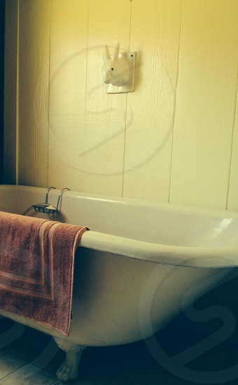 brown bathroom towel on white bathtub photo