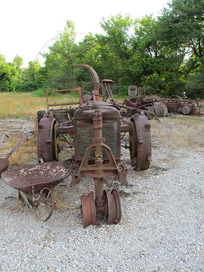 Vintage rusty tractor and wheel barrel. Antique metal photo