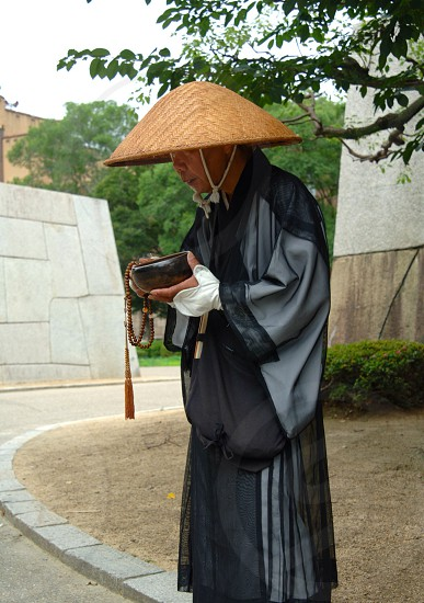 An elderly Asian priest stands at the curb asking for donations for his temple that is desperate need of repairs.  photo