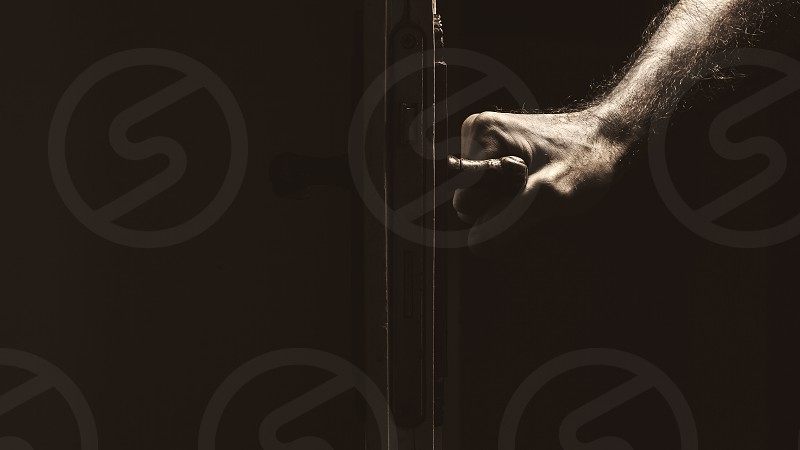 Simple composition male hand on a doorknob dark ambient with accentuated shapes.  photo